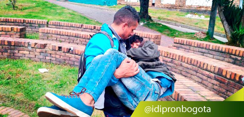 Jóven de IDIPRON lleva en brazo a jóven habitante de calle