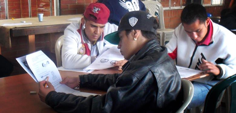 Jóvenes leyendo hojas en examen de convalidación