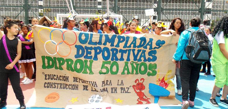 jóvenes idipron sosteniendo cartel de olimpiadas 50 años
